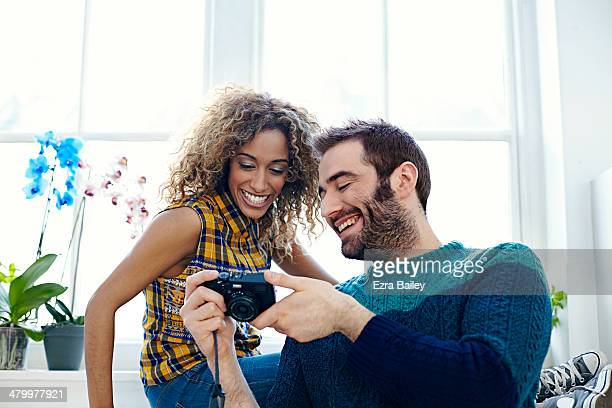 Young couple laughing at photos on digital camera.