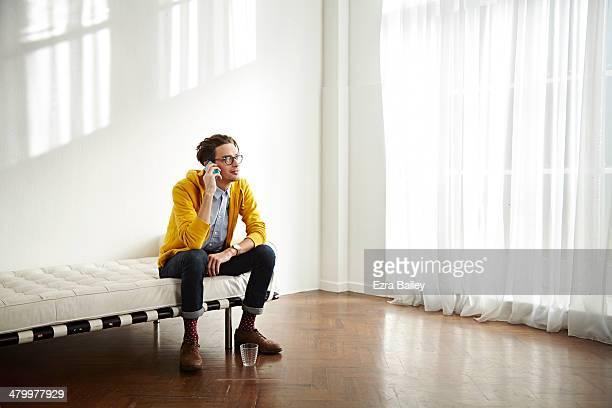 man chatting on his mobile phone in apartment. - nur erwachsene fotos stock-fotos und bilder