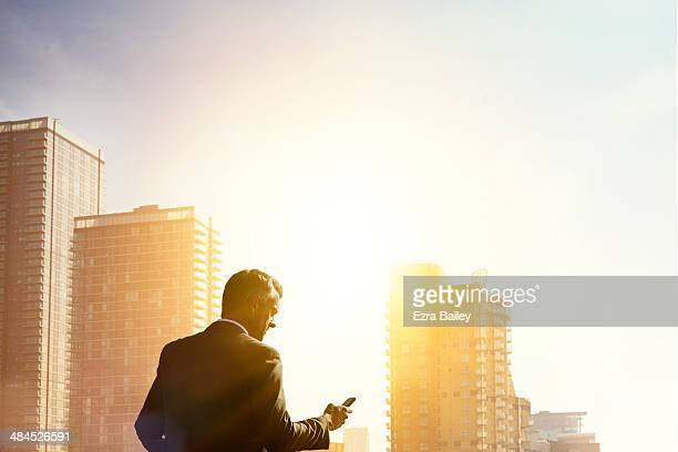 Businessman checking his phone at sunrise.