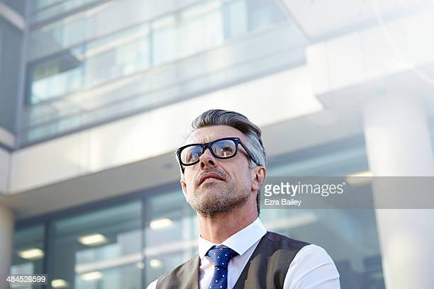 Businessman looking up at a sky scraper.