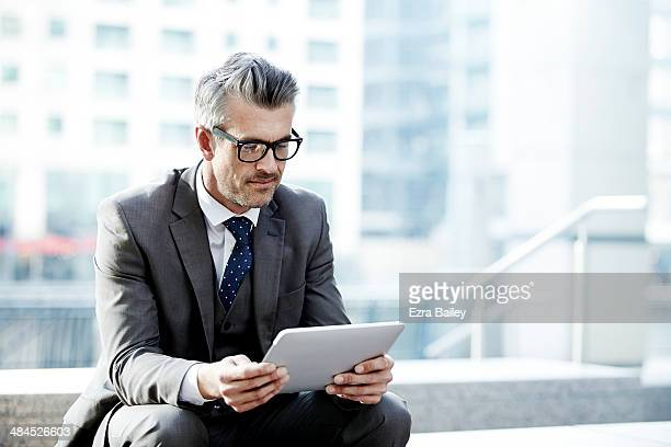 Businessman using a tablet outside in the city.