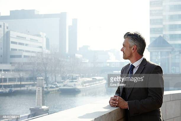 business man looking out over the city. - wealth stock pictures, royalty-free photos & images