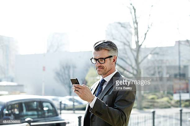 businessman checking his phone in the city. - suit stock pictures, royalty-free photos & images