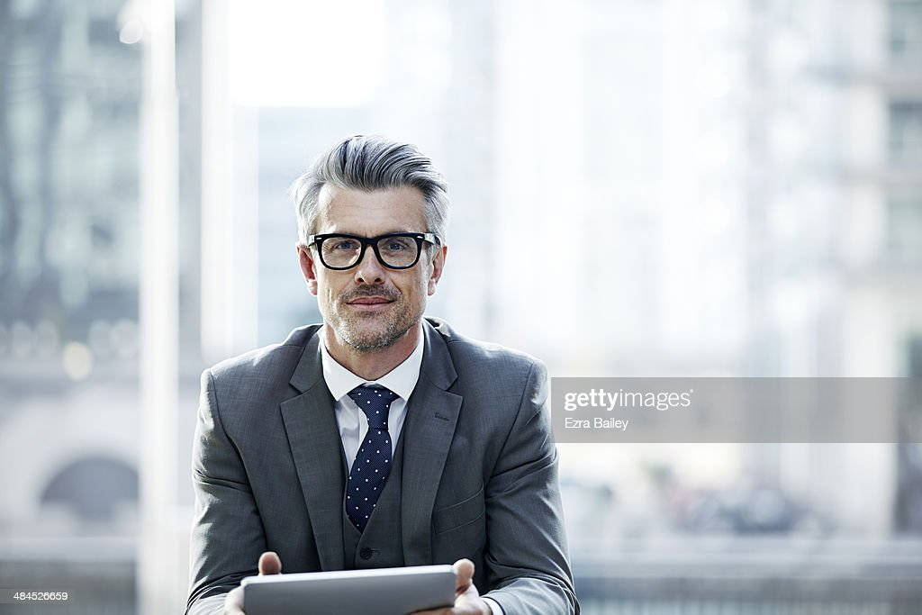 Portrait of a businessman outside holding a tablet : Stock Photo