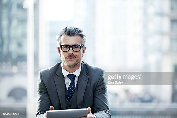 portrait of a businessman outside holding a tablet - full suit stock pictures, royalty-free photos & images