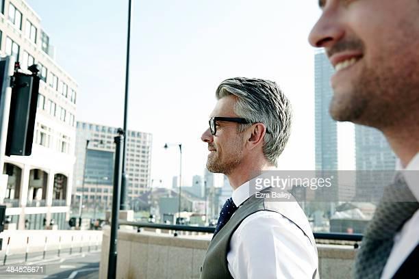 two businessmen talking on the move, in the city. - fianco a fianco foto e immagini stock