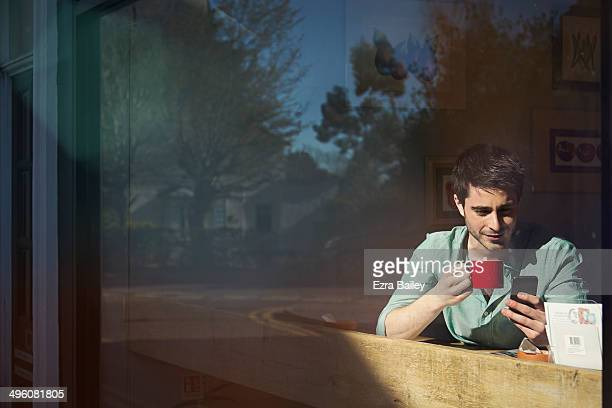 Man looking at him phone in a coffee shop window