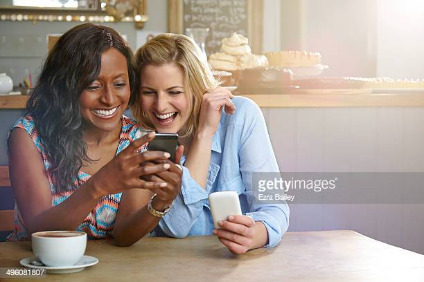 Friends laughing at a phone in a coffee shop