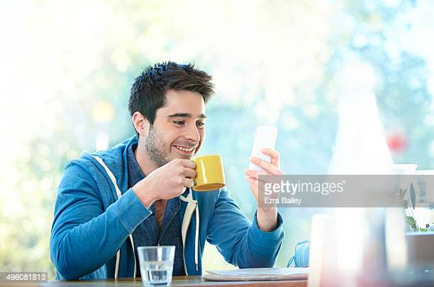 young man using his phone in a cafe. - stubble stock pictures, royalty-free photos & images
