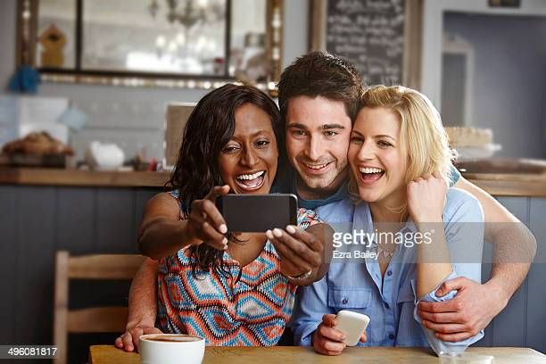 Friends taking a selfie in a coffee shop.