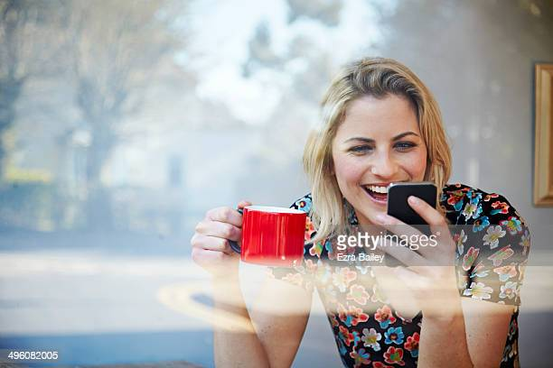 Woman laughing at her phone in coffee shop window.