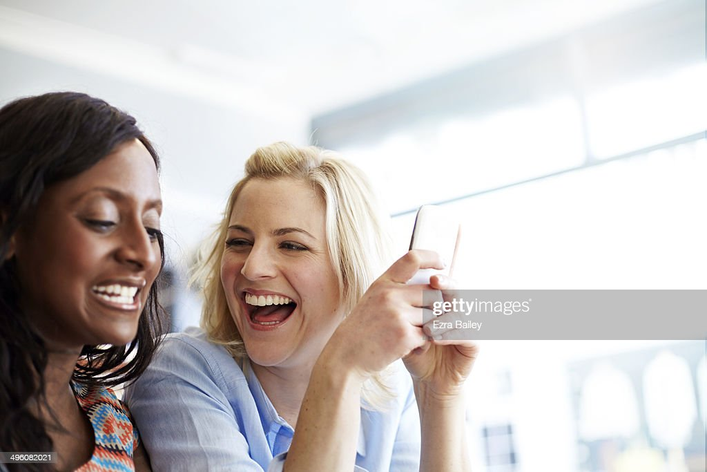 Friends laughing at their phones in a coffee shop. : Stock Photo