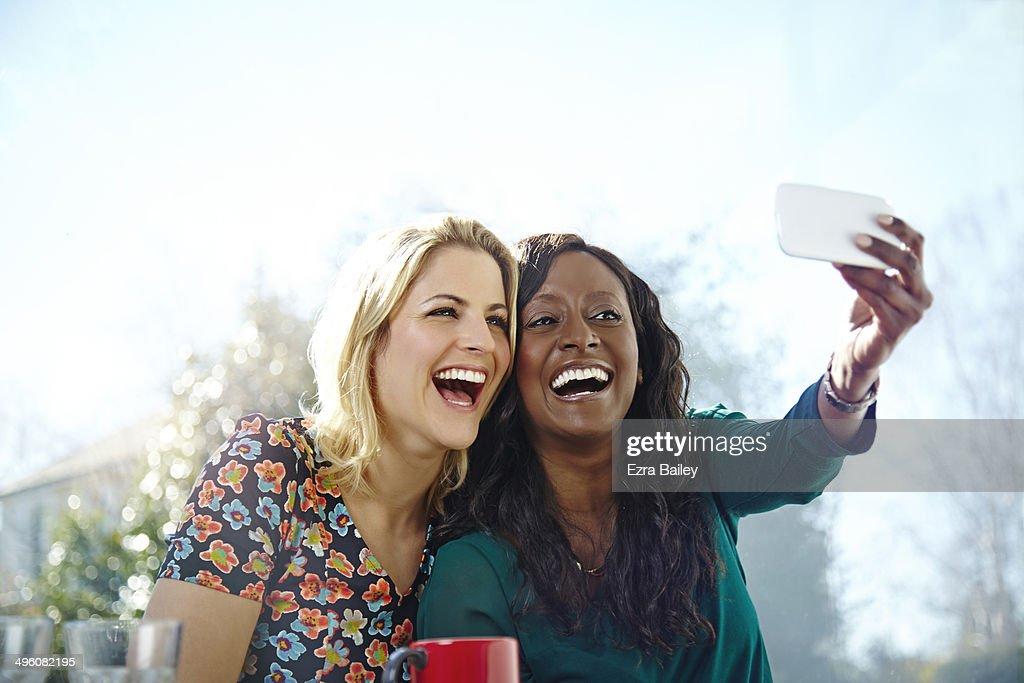 Friends taking a selfie in a coffee shop : Stock Photo