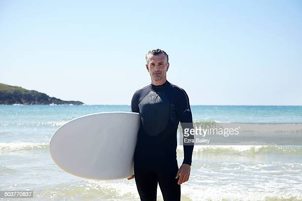 Man in a wetsuit holding a surfboard.