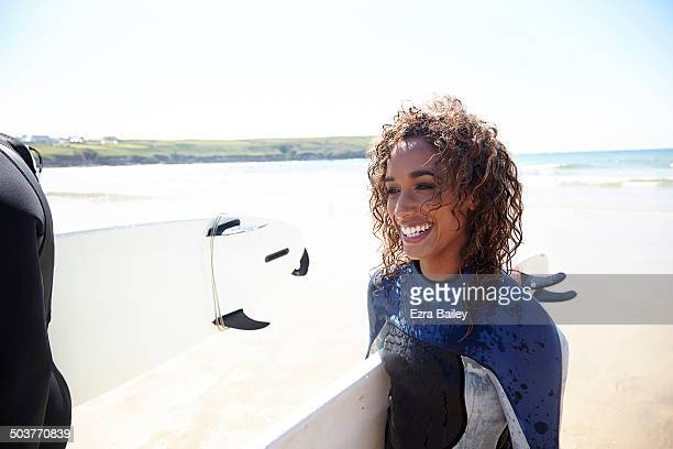 mixed race woman with surfboard walking on the be - curly stock pictures, royalty-free photos & images