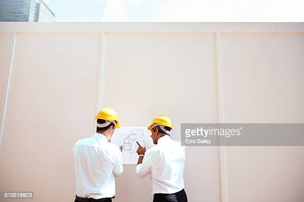 Two architects discussing plans on a building site