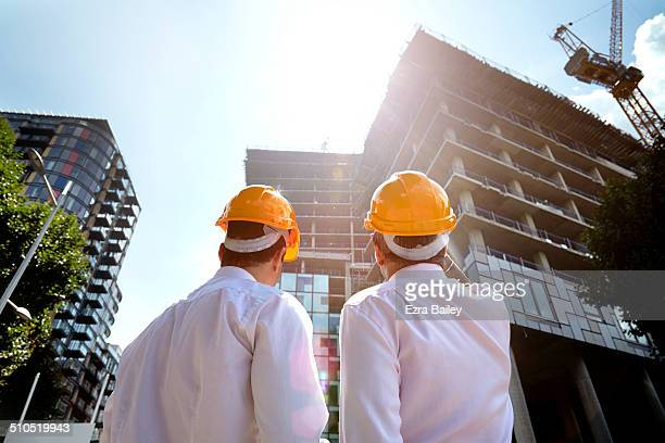 Two architects looking up at development building.