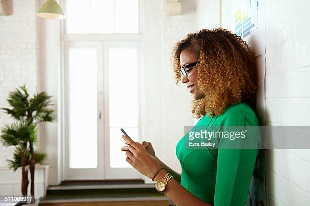 Mixed race woman using a mobile phone in office.