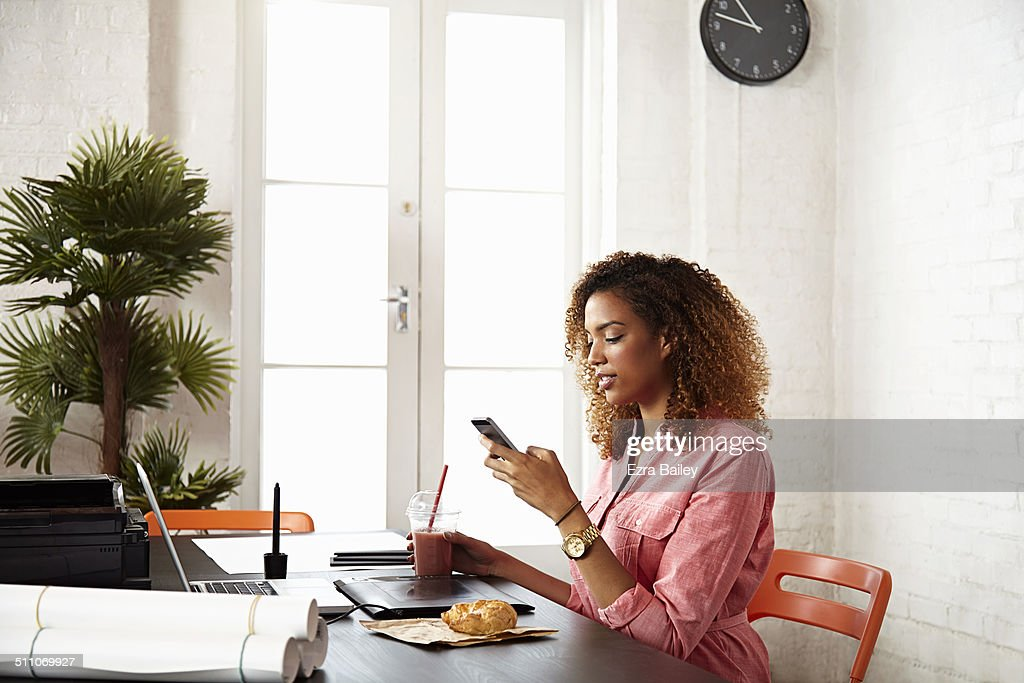 Young women in creative office using a mobile. : Stock Photo