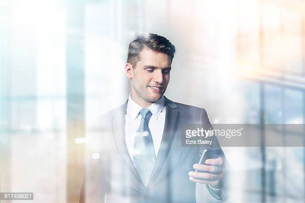 Businessman looking at his phone in modern office.