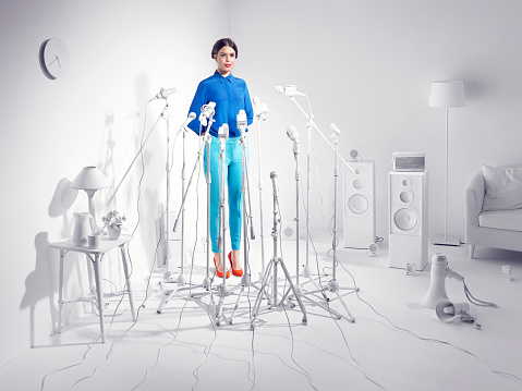 Woman standing in a room of white microphones. - gettyimageskorea