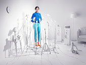 Woman standing in a room of white microphones.