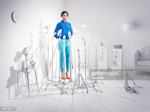 woman standing in a room of white microphones. - politics concept stock pictures, royalty-free photos & images