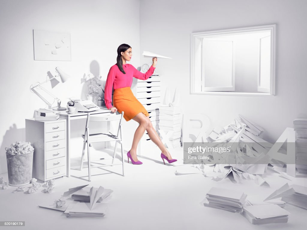 Woman in a white room with paper planes. : Stock Photo