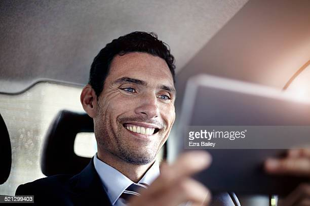 A businessman using a digital tablet in a taxi.