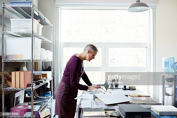 business woman using a laptop in creative space. - older women in short skirts stock pictures, royalty-free photos & images