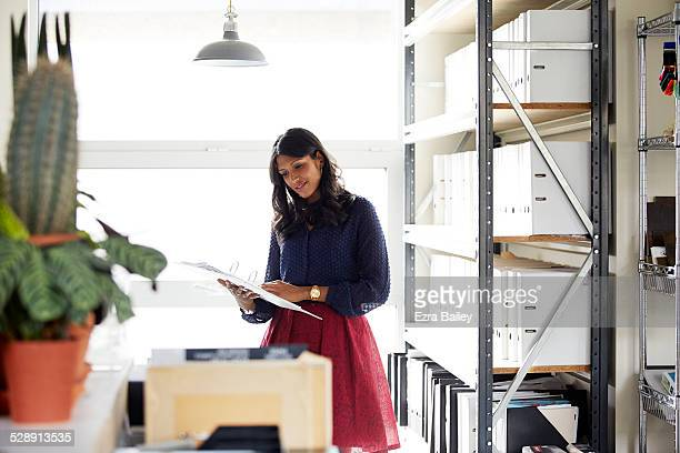Female office worker reading a file by a window.