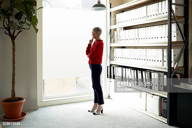 business woman looking out over the city. - red pants stock pictures, royalty-free photos & images