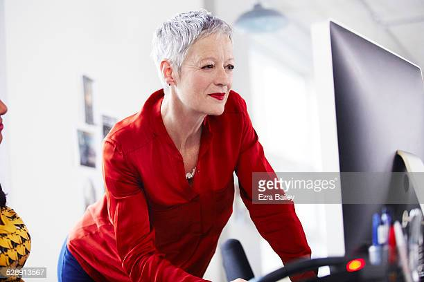 mature businesswoman working on a computer. - red blouse stock pictures, royalty-free photos & images