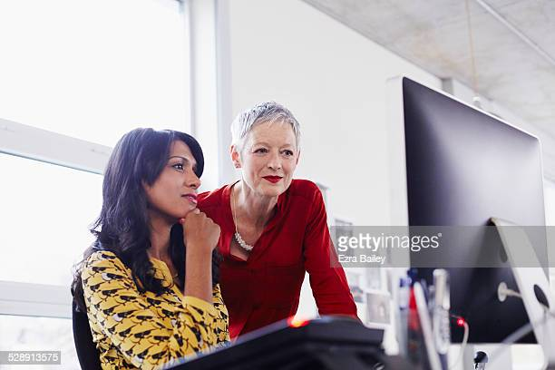 mature business woman mentoring younger employee. - directrice photos et images de collection