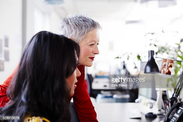 mature business woman mentoring a younger woman. - lipstick stock pictures, royalty-free photos & images
