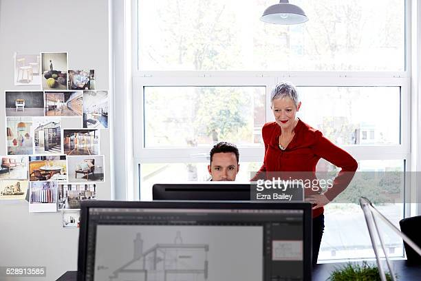mature business woman mentoring younger employee. - red blouse stock pictures, royalty-free photos & images