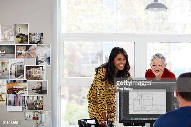 female employees working on a computer - three people stock pictures, royalty-free photos & images