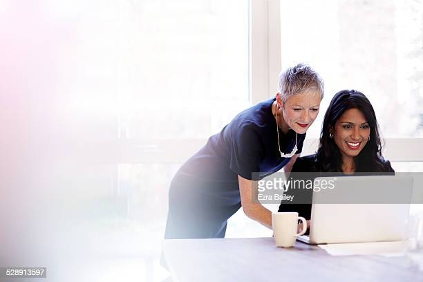 mature business woman mentoring a younger woman. - desk stock pictures, royalty-free photos & images