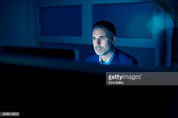 Businessman illuminated by his computer screen
