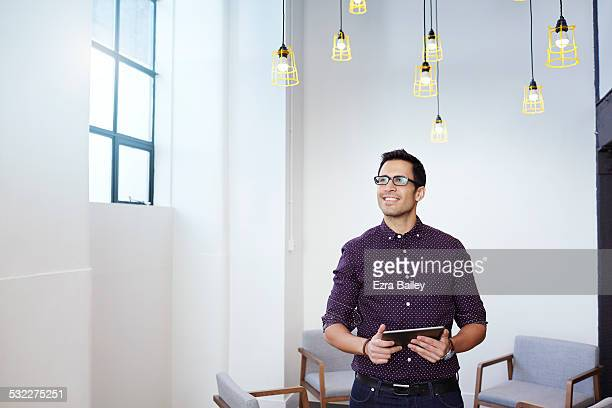 man in open plan office looking out the window. - one man only stock pictures, royalty-free photos & images