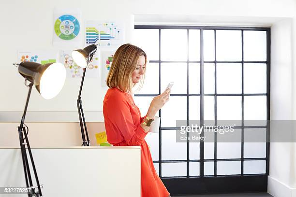 Businesswomen reading emails on her phone.
