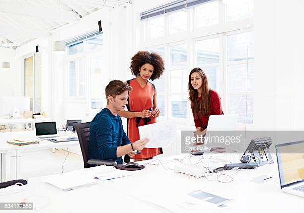meeting in a creative open plan office - three people stock pictures, royalty-free photos & images