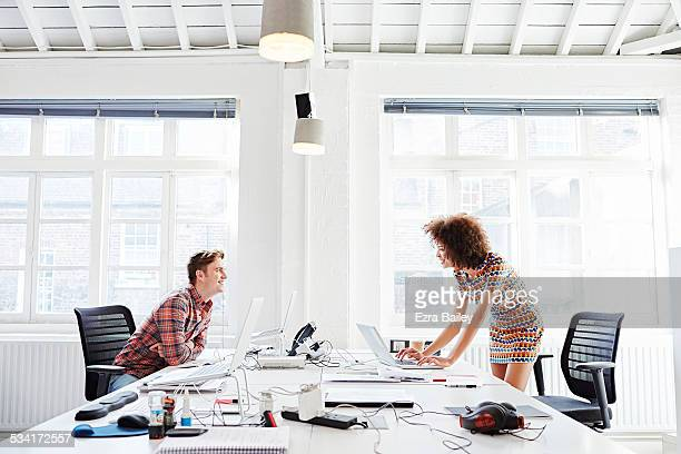Employees chatting informally over their desks.