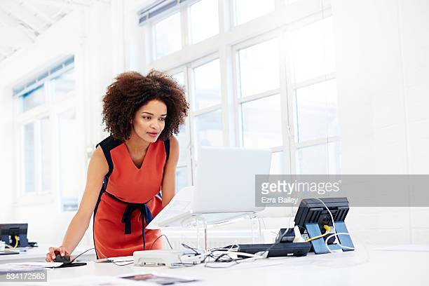 creative woman working in open plan office. - leanincollection stock pictures, royalty-free photos & images