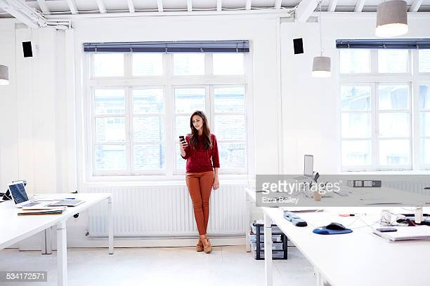 woman texting in modern open plan office - red pants stock pictures, royalty-free photos & images