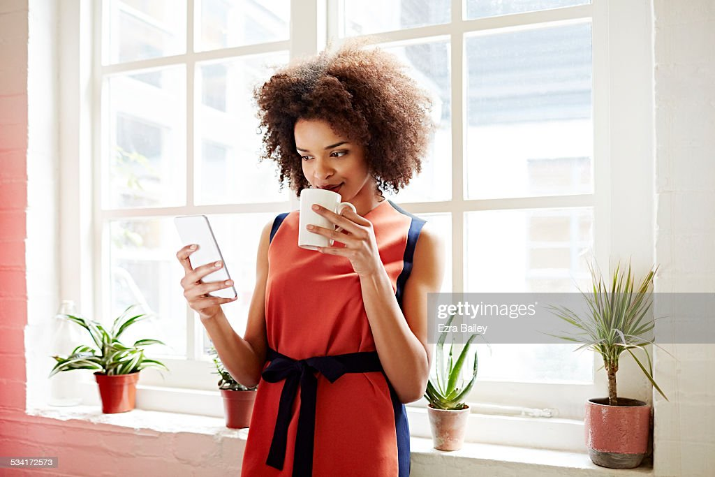 Woman drinking coffee and checking her phone : Stock Photo