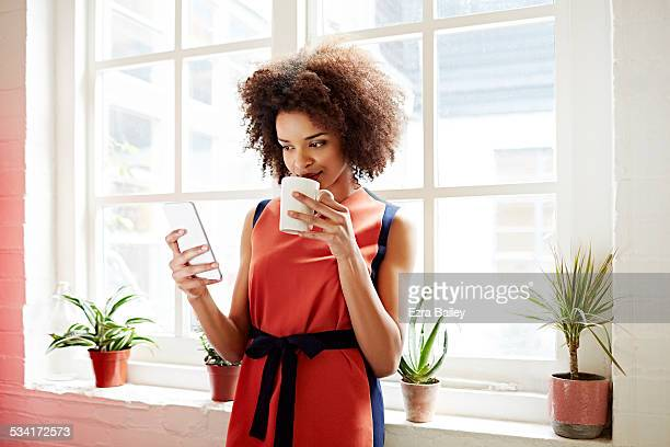 woman drinking coffee and checking her phone - dress stock pictures, royalty-free photos & images