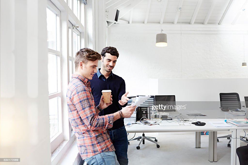 Two creative people chatting in modern office : Stock Photo