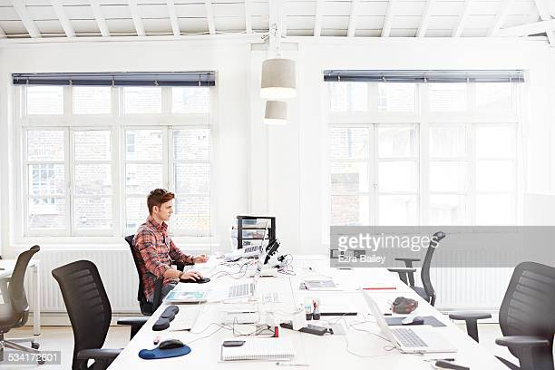Young employee working in modern open plan office.