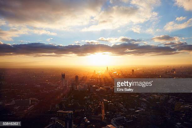 the sun rises through the city on a misty morning. - zonsopgang stockfoto's en -beelden